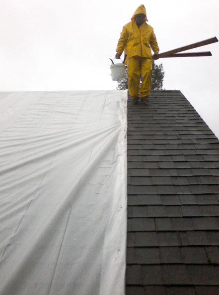 Roofer providing emergency roof leak repair service on a rainy day in the San Francisco Bay Area