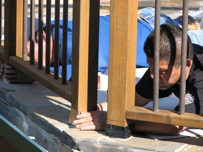 Carpenter installing redwood deck railing on Marin County home