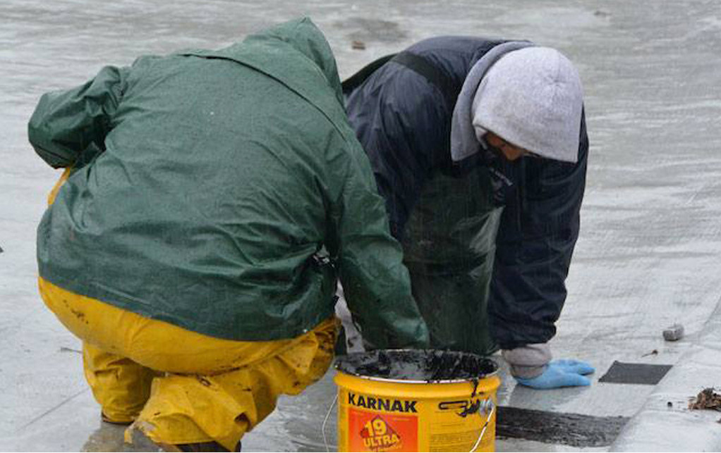 Emergency roof leak repair team at work repairing a roof in the San Francisco Bay Area