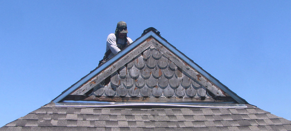 Shingle roof repairs in Marin County with roofer on top of steep slope roof in the San Francisco Bay Area.